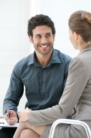 informal: Smiling business man talking with his colleague during an informal meeting at office