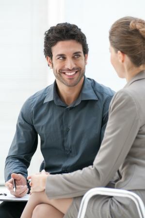 deux personnes qui parlent: Souriant homme d'affaires parle avec son coll�gue lors d'une r�union informelle au si�ge