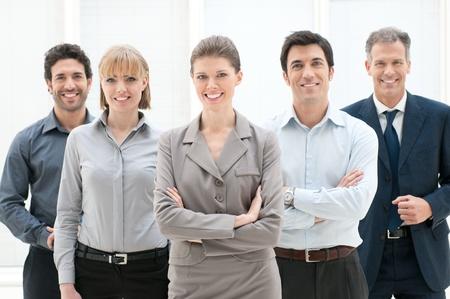 empleado de oficina: Feliz grupo sonriente de hombres de negocios de pie juntos en la oficina