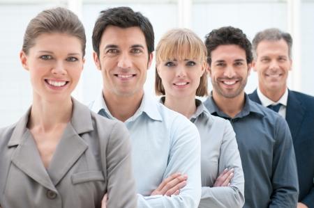Feliz de negocios sonriente equipo de pie en una fila en la oficina Foto de archivo