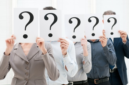 questionmark: Group of business people hiding their faces behind a question mark sign at office Stock Photo