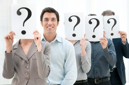 Happy smiling business man standing out of the crowd with other people hiding their face behind a question mark sign