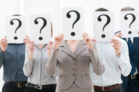 preguntando: Equipo de negocios ocultar sus rostros detrás de las señales de signo de interrogación en la oficina
