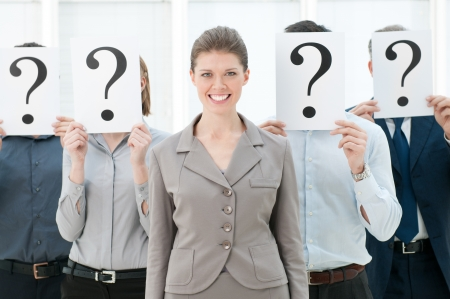 Happy smiling business woman standing out of the crowd with other people hiding their faces behind a question mark sign. Stock Photo - 12669531