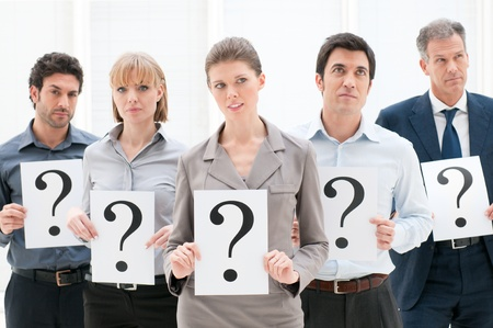 employment issues: Business group of people holding question marks with pensive expression at office