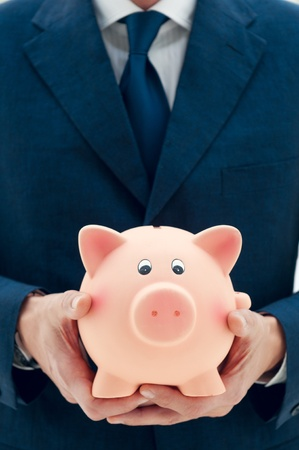 Businessman holding a piggy bank in his hands symbol of savings and good investments photo