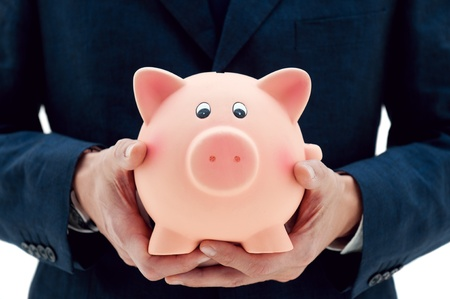 financial advisor: Businessman holding a piggy bank in his hands symbol of savings and good investments