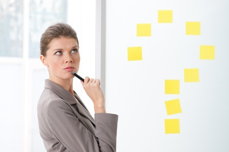BEautiful young business woman with pensive expression near a question mark sign of post it photo