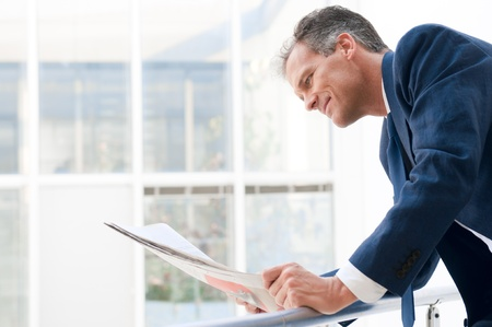 Mature businessman looking and reading newspaper in a modern office Stock Photo - 12669486
