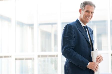 spokojený: S úsměvem spokojený senior podnikatel při pohledu na fotoaparát v kanceláři