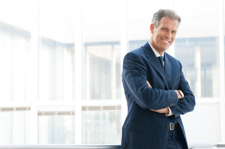 mature business man: Happy mature business man looking at camera with satisfaction at office