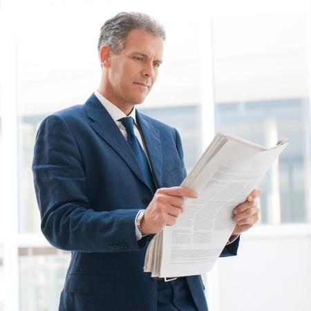成熟したビジネス男がオフィスでニュースを読む