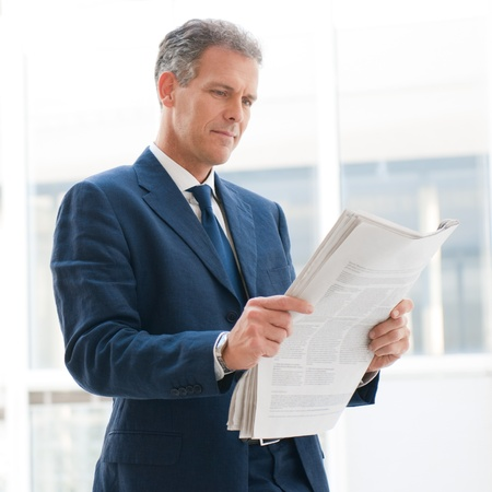 Mature business man reading news in the office Stock Photo - 12669453