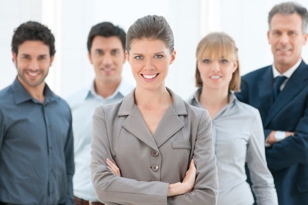 proud: Happy smiling business woman looking at camera with her colleagues at office Stock Photo