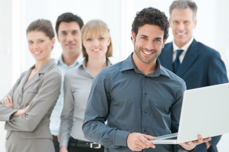 work together: Happy zakelijke man die een moderne laptop computer met zijn team op de achtergrond