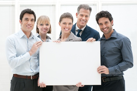 Happy smiling business team holding a blank placard ready for your text or product photo
