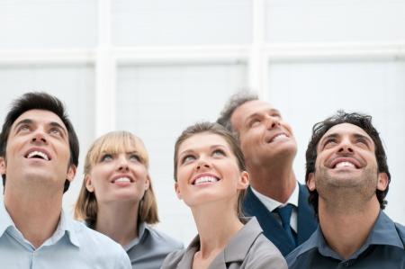 vision futuro: Feliz grupo empresarial positivo mirando hacia arriba con expresión de soñar