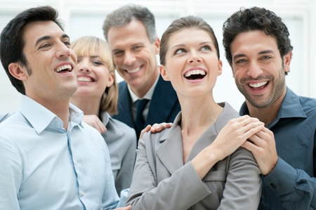 laughing girl: Happy business team smiling and laughing together at office to celebrate a success Stock Photo