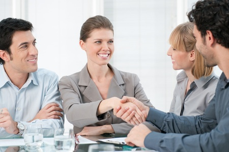 business deal: Happy smiling businesswoman shaking hands after a business meeting