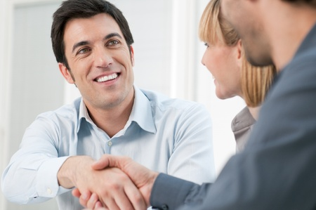 deal in: Happy smiling business man shaking hands after a deal in office