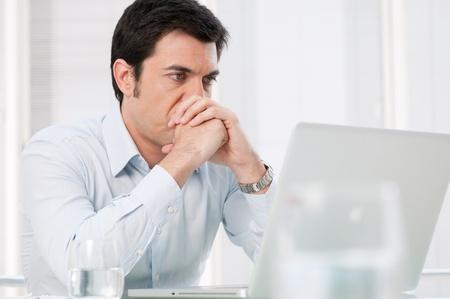 hombre preocupado: Pensativo hombre de negocios absorbida mirando al ordenador port�til con expresi�n preocupada