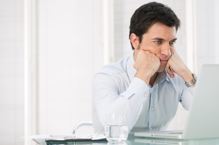 Worried pensive business man watching at his laptop at office Stock Photo - 13025721