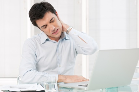 back to work: Businessman with neck pain after long hours at work