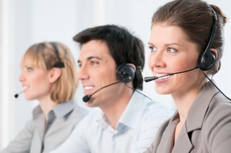 hotline: Glimlachende mooie dame werken bij callcenter met collega's in het kantoor