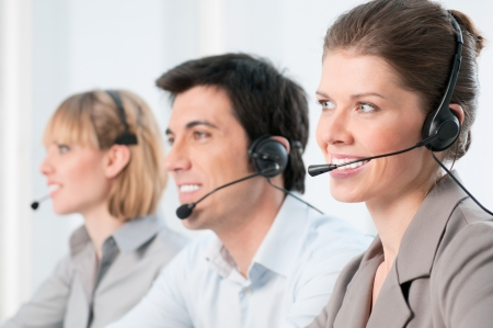 call center agent: Smiling beautiful lady working at call center with colleagues in office