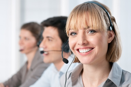Smiling lady working at call center office with colleagues photo