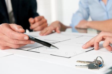agente: Closeup vista di nuove chiavi di casa e il piano casa durante una discussione con un agente immobiliare