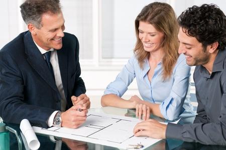 agente: Felice giovane coppia a discutere con un agente immobiliare dei loro piani nuova casa
