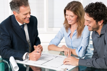 agents: Happy young couple discussing with an estate agent about their new house plans Stock Photo