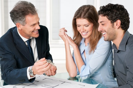 Happy estate agent showing new home keys to a young couple after a discussion on house plans