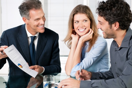 Financial consultant presenting a business investment to a smiling young couple photo