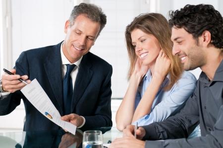 abogado: Feliz pareja joven discutiendo con un agente financiero de sus nuevas inversiones