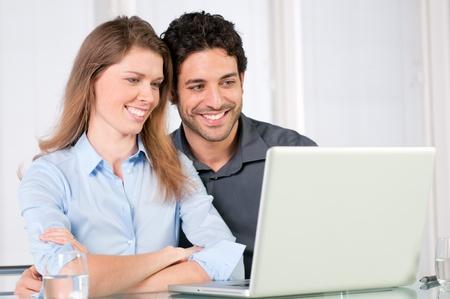 tabla de surf: Feliz pareja joven y sonriente mirando juntos en un ordenador port�til Foto de archivo