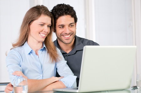 Happy smiling young couple watching together at computer laptop photo