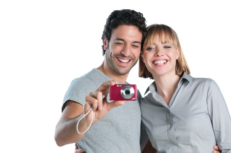 Happy smiling couple having fun with photograph isolated on white background photo