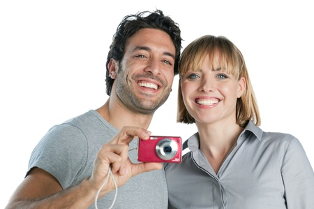 Happy joyful couple taking pictures with digital camera isolated on white background photo