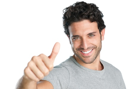 Happy smiling guy showing thumb up hand sign isolated on white background photo