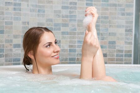 Young beautiful woman having a bath with soap photo