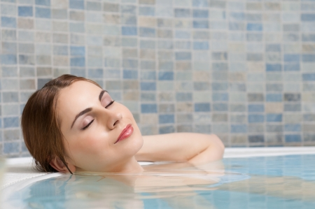 resting: Beautiful young lady relaxing during a bath in a pool at thermal club Stock Photo