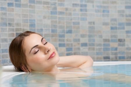 baÑo: Joven y bella dama relajarse durante un baño en una piscina en el club termal