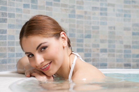 Beautiful young lady in a hot tub of a beauty center photo