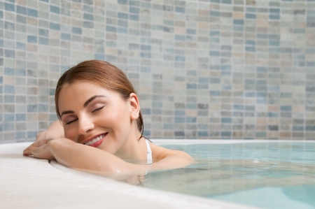 Beautiful relaxed woman stay at the edge of a hot pool at spa club photo