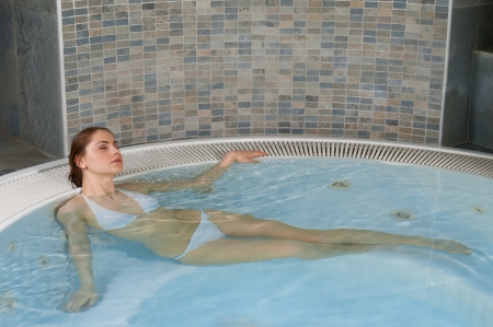 Beautyful young woman relaxing in a jacuzzi hot tub at spa photo