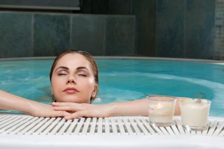 stay beautiful: Relajado mujer hermosa �venes permanecer en el borde de una piscina en el spa del club