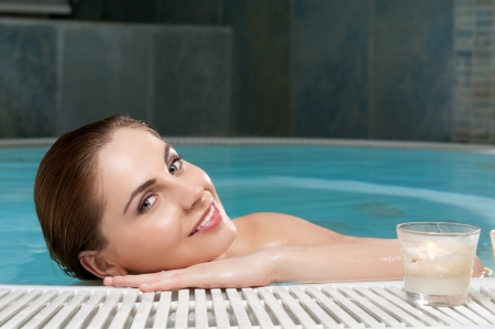 Smiling young woman stay at the edge of a hot tub in a beauty spa center photo