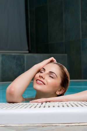 Beautiful young woman relaxing at the edge of a pool at health club Stock Photo - 13741933
